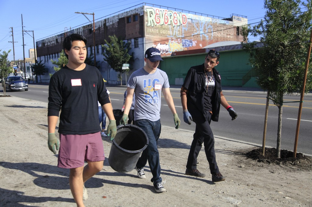 Downtown Los Angles Neoghborhood Councilmember and Skid Row resident, Eric Dean (right) workking with UCLA students to care for trees on Alameda Street in Downtown Los Angeles.