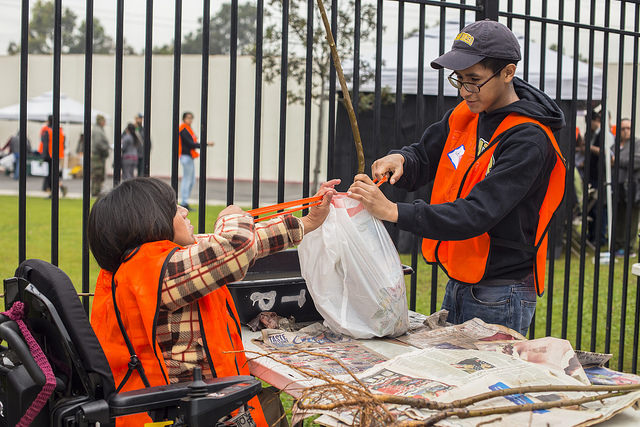 Volunteers in Huntington Park prepare a tree for transport